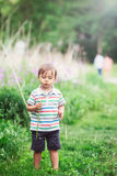 Portrait of a cute funny little boy toddler standing in the forest field meadow with dandelion flowers in hands. And blowing them on a bright summer day, summer Royalty Free Stock Image