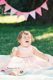 Portrait of cute funny upset sad crying Caucasian baby girl in pink tutu dress celebrating her first birthday. With gourmet cake outside in park, cake smash Stock Image