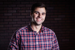 Portrait of cute funny young guy in a plaid shirt. Cute young guy in a plaid shirt smiling Royalty Free Stock Photos