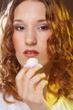 Portrait of a cute girl in act to eat a candy. Beauty portrait of a cute girl in act to eat a candy with cocoanut stock image