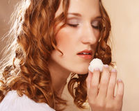 Portrait of a cute  girl in act to eat a candy. Beauty portrait of a cute  girl in act to eat a candy with cocoanut Stock Photos