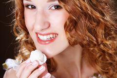 Portrait of a cute  girl in act to eat a candy. Beauty portrait of a cute  girl in act to eat a candy with cocoanut Royalty Free Stock Photography