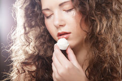 Portrait of a cute  girl in act to eat a candy. Beauty portrait of a cute  girl in act to eat a candy with cocoanut Stock Photo