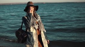 Portrait of cute girl in autumn coat against the sea. girl posing at camera and smiling stock video footage