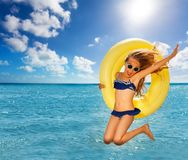 Cute girl jumps for joy with big swimming ring. Portrait of cute girl in bikini and sunglasses jumps for joy with big yellow swimming ring against the sea Royalty Free Stock Photos