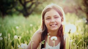 Portrait of cute girl blow on a dandelion in garden at sunset stock video footage