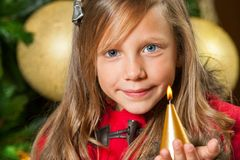 Portrait of cute girl with candle. Portrait of cute little girl holding candle at christmas tree Royalty Free Stock Image