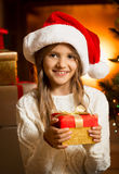 Portrait of cute girl with Christmas gift at fireplace Royalty Free Stock Image