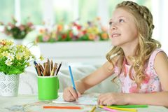 Girl drawing at home. Portrait of a cute girl drawing at home stock images