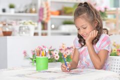 Portrait of a cute girl drawing picture at home stock image