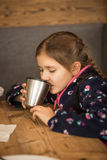 Portrait of cute girl drinking tea from thermos at cafe Royalty Free Stock Photography