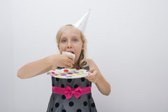 Portrait of cute girl eating birthday cake slice at table in house Royalty Free Stock Images