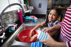 Portrait of cute girl helping her mother in kitchen. Portrait of cute smiling girl helping her mother in kitchen at home Stock Images