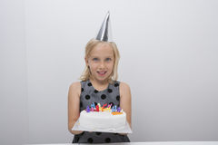 Portrait of cute girl holding birthday cake at home Royalty Free Stock Photography