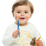 Cute girl holding color wax crayons. Stock Image
