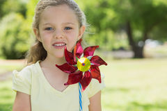 Portrait of cute girl holding pinwheel at park Stock Photos