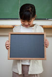Portrait of a cute girl holding a school slate Royalty Free Stock Image