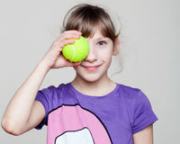 Portrait of a cute girl holding a tennis ball at the eye Stock Photo