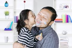 Cute girl kisses her father at home Royalty Free Stock Images
