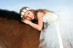 Portrait of cute girl laying on horseback. Royalty Free Stock Photography