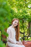 Portrait of a cute girl with long red hair in the park stock images