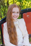 Portrait of a cute girl with long red hair in the park. Beautiful redhead girl in a blossoming summer garden Stock Photos