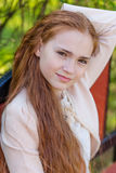 Portrait of a cute girl with long red hair in the park. Beautiful redhead girl in a blossoming summer garden Royalty Free Stock Photos