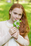 Portrait of a cute girl with long red hair in the park. Beautiful redhead girl in a blossoming summer garden. A child with a flower in his hands Stock Image