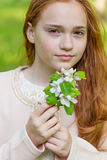 Portrait of a cute girl with long red hair in the park. Beautiful redhead girl in a blossoming summer garden. A child with a flower in his hands Stock Photos