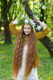 Portrait of a cute girl with long red hair in the park. Beautiful redhead girl in a blossoming summer garden. Redhead child with a flower in his hair Royalty Free Stock Photos