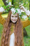 Portrait of a cute girl with long red hair in the park. Beautiful redhead girl in a blossoming summer garden. Redhead child with a flower in his hair Stock Photography