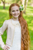 Portrait of a cute girl with long red hair in the park. Beautiful redhead girl in a blossoming summer garden. Redhead child with a flower in his hair Royalty Free Stock Photo