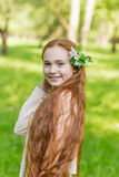 Portrait of a cute girl with long red hair in the park. Beautiful redhead girl in a blossoming summer garden. Redhead child with a flower in his hair Royalty Free Stock Image