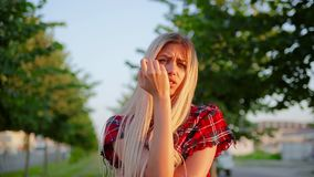 Portrait cute girl with long white hair is angry very and looks with great disappointment and nervously straightens her hair. Standing on alley with blurred stock video footage