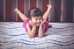 Portrait of cute girl lying barefoot on bed in bedroom. Stock Image