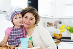 Portrait of cute girl and mother in kitchen Stock Images