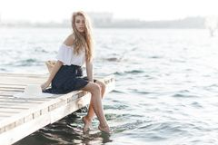 Portrait of a cute girl outdoors in sitting on a pier in the spring. Happy woman on the beach. Portrait of a beautiful girl close-up. Spring portrait on the royalty free stock image