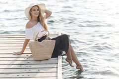 Portrait of a cute girl outdoors in sitting on a pier in the spring. Happy woman on the beach. Portrait of a beautiful girl close-up. Spring portrait on the royalty free stock photo
