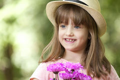 Portrait of a cute girl in a park, holding a bouquet of flowers Royalty Free Stock Photography