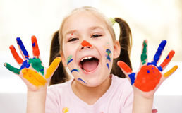 Portrait of a cute girl playing with paints Stock Photos