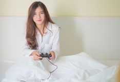 Portrait of a cute girl playing video games while she is lying o Stock Photo