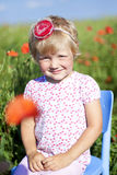Portrait of cute girl in poppy fied. Portrait of cute girl in poppy field during hot summer day Royalty Free Stock Photo
