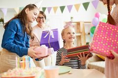 Children giving Birthday Gifts. Portrait of cute girl receiving gifts surrounded by friends a during Birthday party, copy space royalty free stock photos