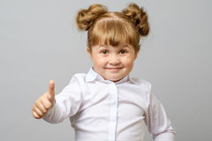 Portrait of cute girl showing thumbs up sign royalty free stock photography