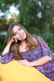 Portrait of cute girl sitting in chair and smiling in photograph Royalty Free Stock Image