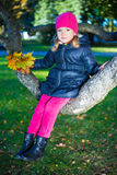 Portrait of cute girl sitting on tree branch in autumn park Stock Photography