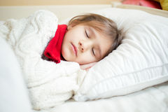 Portrait of cute girl in sweater and scarf lying on white pillow Stock Image