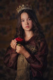 Portrait of cute girl wearing a crown with a rose in hands. Young queen or princess. Stock Image