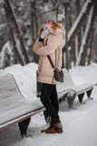 Portrait of cute girl in winter park standing on alley, smiling Stock Images