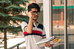 Portrait of a cute glamorous student in glasses with books Royalty Free Stock Photo